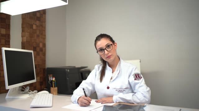 vídeos de stock, filmes e b-roll de doutor fêmea que senta-se na mesa na clínica - dermatologia