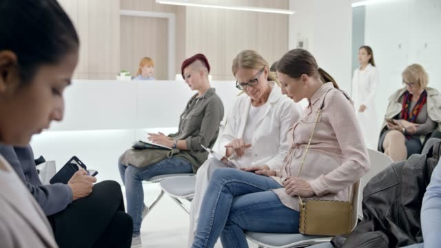 ds female doctor sitting next to her pregnant female patient in the waiting room and  giving her good news - next to stock videos and b-roll footage