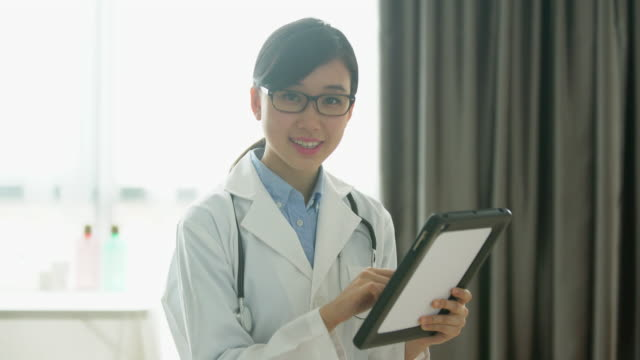 MS female doctor smiling and working on digital tablet