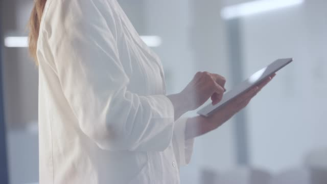 female doctor standing in the hallway and scrolling the digital tablet - dottoressa video stock e b–roll