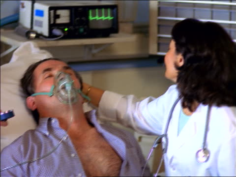 Female doctor stroking forehead of middle-aged patient with oxygen mask / nurse takes blood pressure