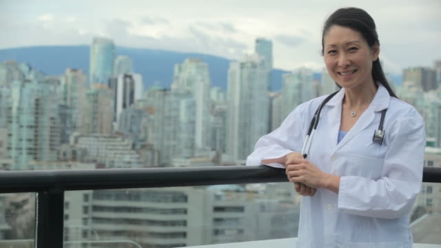 ms pan female doctor surgeon standing at balcony of building / vancouver, bc, canada - female doctor stock videos & royalty-free footage