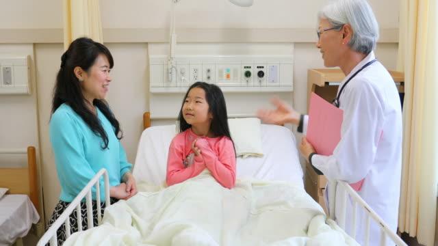 病院のベッドで病気の子供と話す女性医師 - 小児科医点の映像素材/bロール