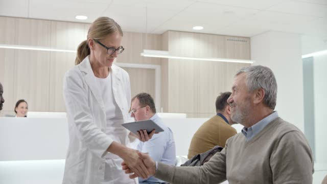 female doctor talking to her male patient, wishing him a nice day and walking out of the waiting room - 50 54 years stock videos & royalty-free footage