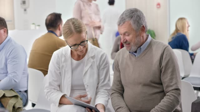 female doctor talking to her senior male patient in the waiting room while looking at the digital tablet - sala d'attesa video stock e b–roll