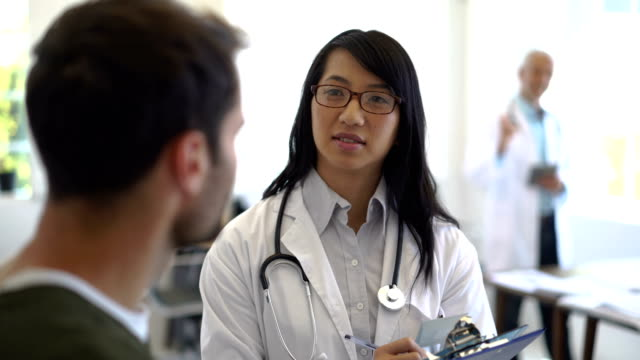 Female doctor talking to male patient in clinic