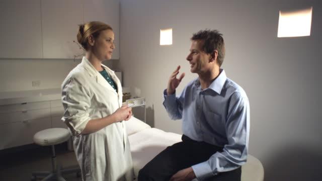MS, Female doctor talking to male patient in office, Sydney, Australia
