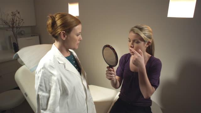 ZI, MS, Female doctor talking to patient looking into hand-held mirror, Sydney, Australia