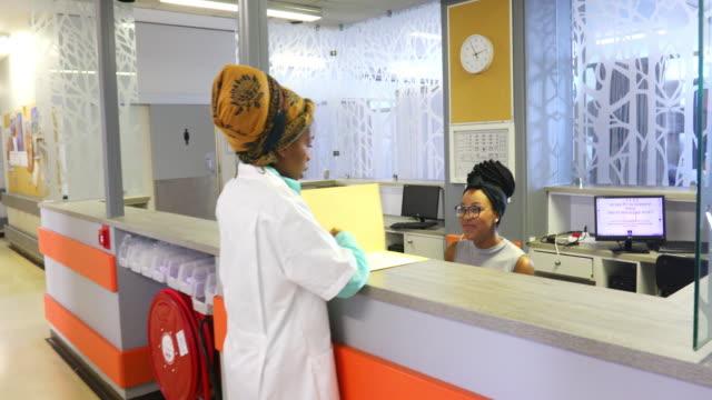 vidéos et rushes de docteur féminin parlant au réceptionniste à un hôpital - salle d'attente