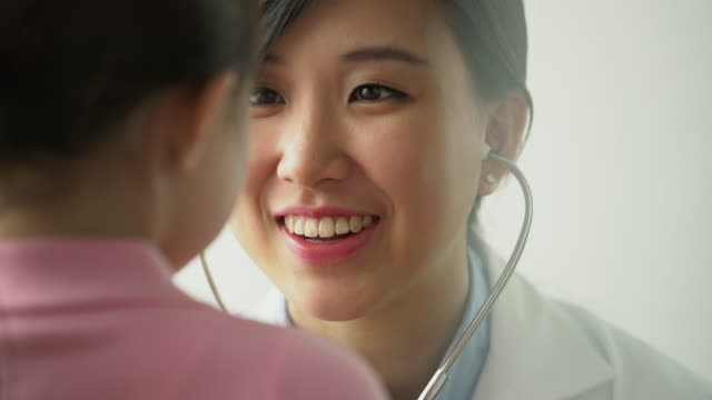 cu female doctor talking to young patient - asiatischer und indischer abstammung stock-videos und b-roll-filmmaterial