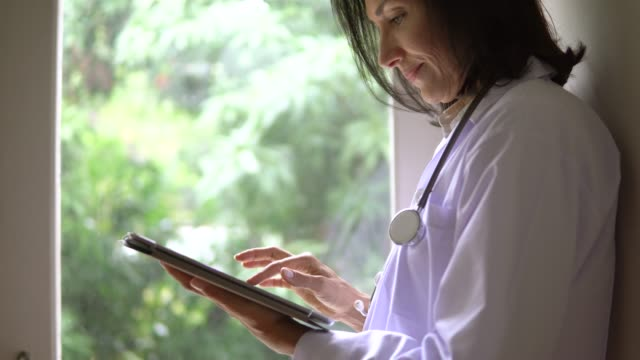 female doctor using digital tablet computer - female doctor stock videos & royalty-free footage