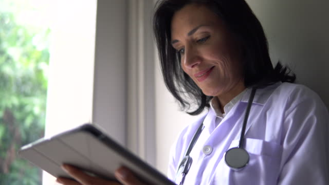 medico donna che utilizza tablet digitale con stetoscopio - doctor video stock e b–roll