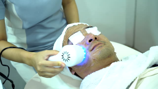 vídeos de stock e filmes b-roll de 4k female doctor using ipl blue light to sterilize acne on young male face at beauty clinic - depilação