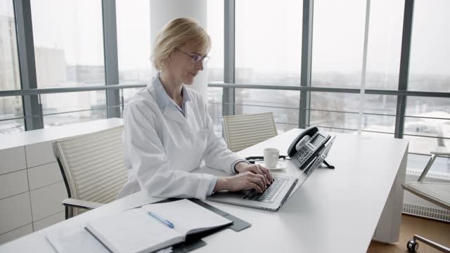 ärztin mit laptop in ihrer arztpraxis - ärztin stock-videos und b-roll-filmmaterial
