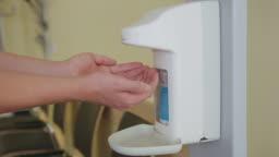 Female doctor using sanitizer in hospital