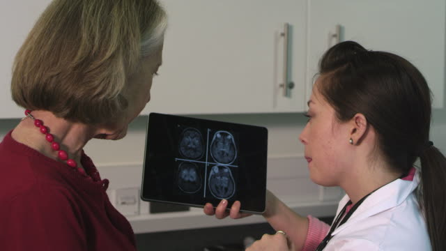 Female doctor using tablet and discussing with patient