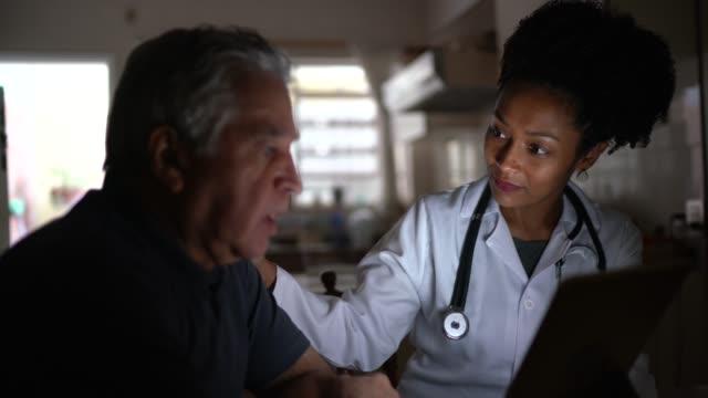 vidéos et rushes de médecin féminin visitant son patient à son domicile - rendez-vous avec la tablette numérique - visite à domicile