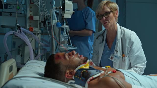 DS kvinna läkare besöker hennes unga manliga patienten på IVA