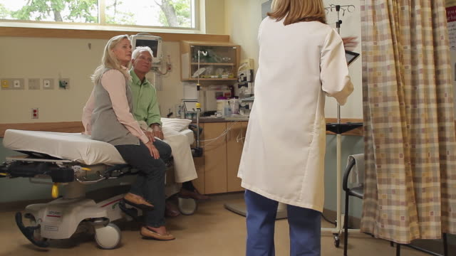 ws female doctor visiting patient in hospital room / portland, maine, usa - laborkittel stock-videos und b-roll-filmmaterial