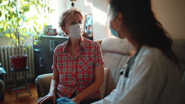 female doctor visiting senior woman at her home - house call stock videos & royalty-free footage