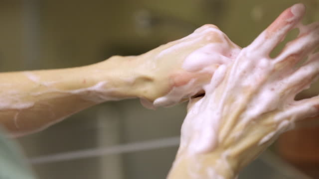 cu of female doctor washing her hands with scrub sponge - medizinerkleidung stock-videos und b-roll-filmmaterial