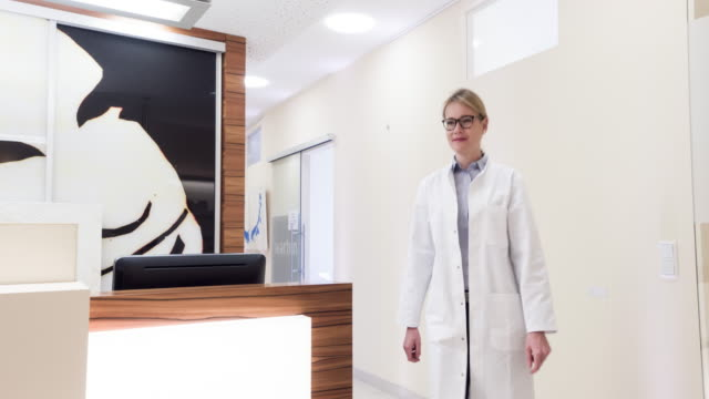 female doctor welcoming patient - praxis stock-videos und b-roll-filmmaterial