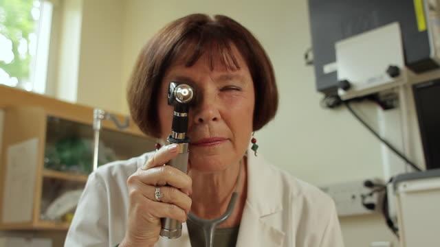 POV CU Female doctor with otoscope / Portland, Maine, USA