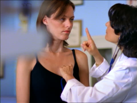 vídeos de stock e filmes b-roll de female doctor with stethoscope checking heart of female patient in tank top - ouvir o batimento cardíaco