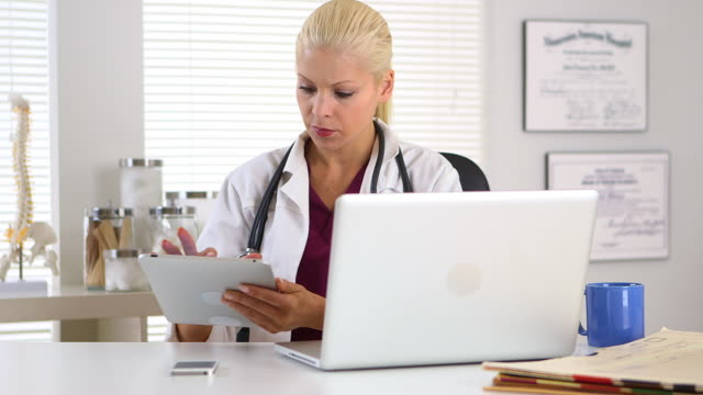 female doctor working on tablet and laptop computer - doctor multitasking stock videos & royalty-free footage