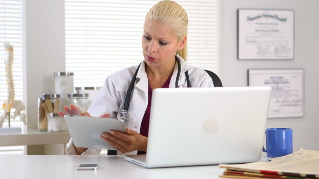 female doctor working on touchscreen and laptop computer - doctor multitasking stock videos & royalty-free footage
