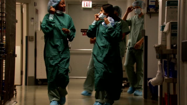 vídeos de stock e filmes b-roll de female doctors and nurses in scrubs walking in corridor smiling - enfermeira