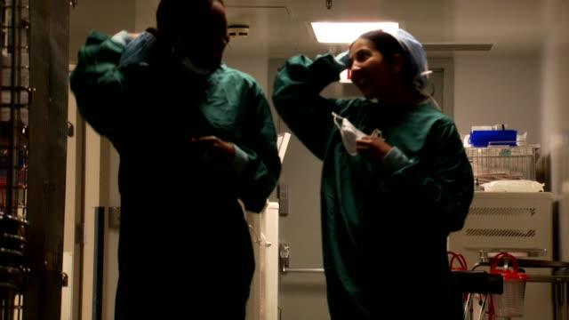 vidéos et rushes de female doctors in scrubs walking in corridor smiling - féliciter