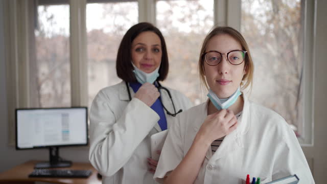 female doctors taking off their protective face mask, after they finished with their daily shift - laboratory coat stock videos & royalty-free footage