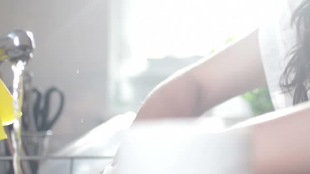 vídeos de stock e filmes b-roll de mulher fazendo pratos na cozinha doméstica - porta sabonete líquido