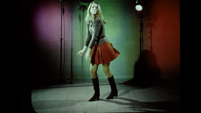 vídeos de stock, filmes e b-roll de hd female dressed in sweater skirt boots drop frames stop motion dancing in lighted studio w/ magenta green red lighting on wall bg 1960s free form... - 1960 1969