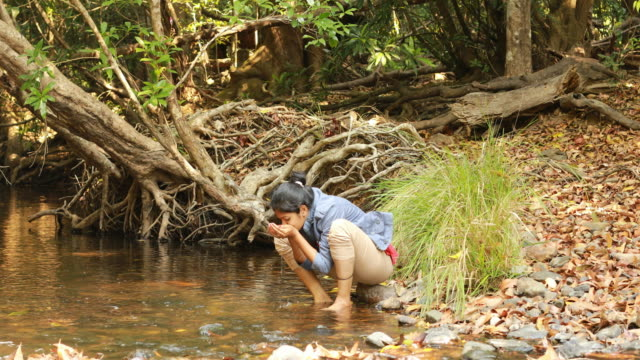Female Drinking River Water