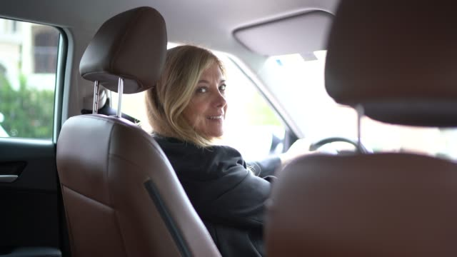 female driver looking over the should into the camera - part of a series stock videos & royalty-free footage