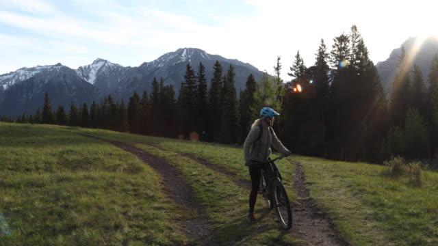 female e-bike rider follows pathway, below mountains - サイクリングロード点の映像素材/bロール
