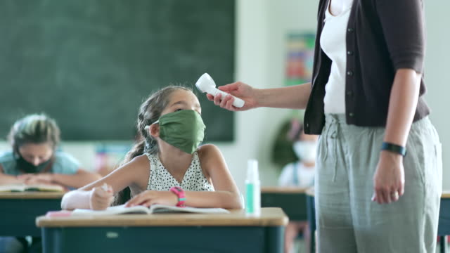 Female educator checks students temperature