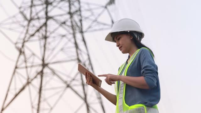 vidéos et rushes de ingénieur électrique féminin travaillant sur la tablette numérique avec le fond électrique de poteau électrique - signalisation