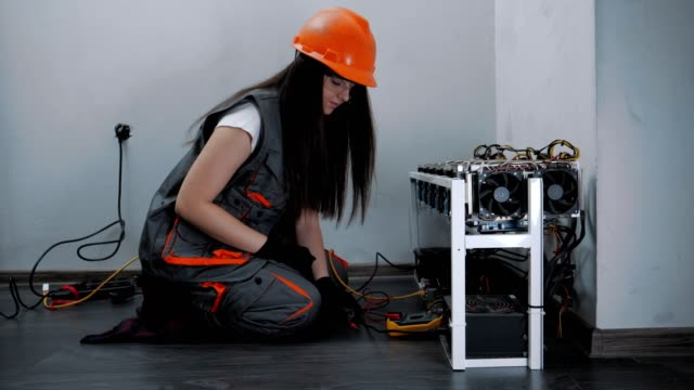 Female Electrician Working on an IT item, Engineering, Measuring Electrical Resistance, Professional IT Support, Technology, STEM, Experienced Professional