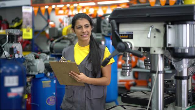 Kvinnlig anställd i en järnaffär som gör inventering av maskiner