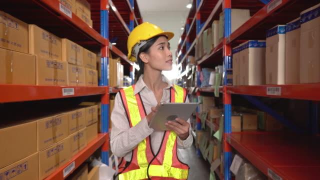 デジタルタブレットで注文の詳細を確認する女性従業員 - 貯蔵庫点の映像素材/bロール