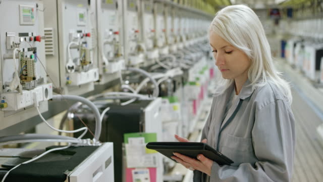 female employee checking the data on the screens of the machines doing product testing in the factory - indoors stock videos & royalty-free footage