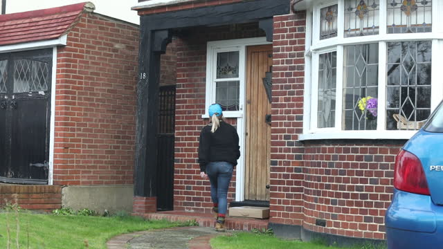 female employee delivers an amazon package to suburban house in southend, westcliff-on-sea and leigh-on-sea, essex, uk on thursday, november 26, 2020. - delivering stock videos & royalty-free footage
