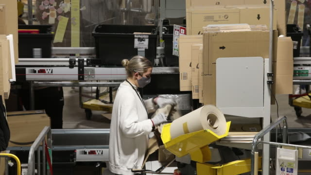 female employee in a face mask packs a box at the amazon warehouse in kegworth, uk ahead of amazon prime day event on monday, october 12, 2020. - cardboard box stock videos & royalty-free footage