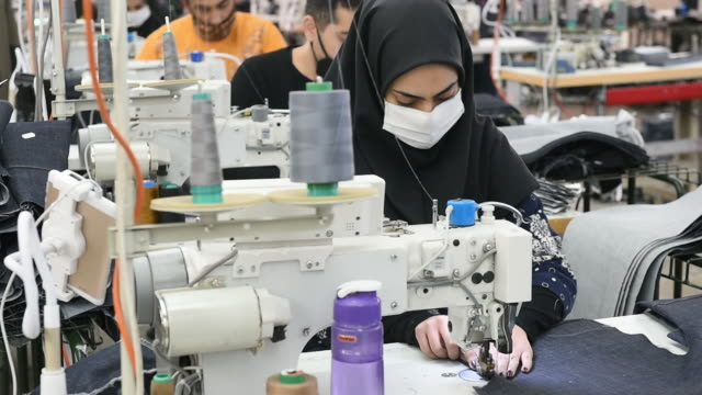 female employee in hijab and face mask during work in clothing factory in tehran. workers wearing protective face masks manufacture iranian brand... - maßkonfektion stock-videos und b-roll-filmmaterial