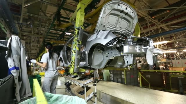 vídeos de stock, filmes e b-roll de a female employee looks at car parts at a renault dacia factory in pitesti romania on thursday july 3 employees fit a part to the underneath of a... - produto interno bruto