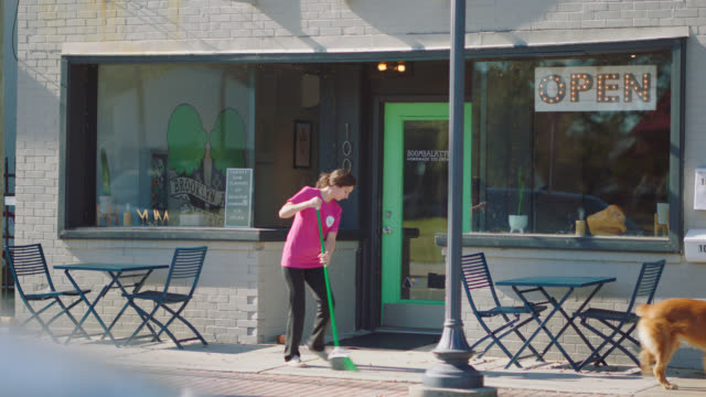 female employee of an ice cream parlor sweeps the sidewalk in front - employee stock videos & royalty-free footage
