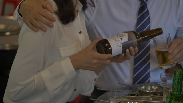female employee pouring beer into a glass - menschliches gelenk stock-videos und b-roll-filmmaterial